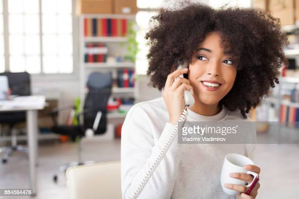 Smiling female assistant using landline phone in modern office