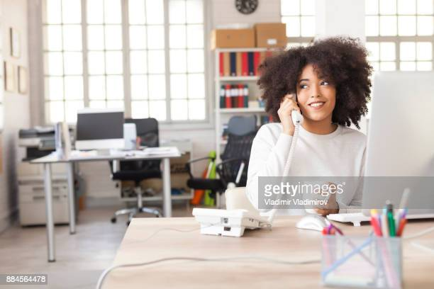 smiling female assistant using landline phone in modern office - landline phone stock pictures, royalty-free photos & images