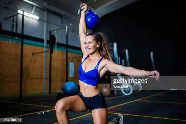 smiling female athlete lifting kettle while kneeling in gym - picking up stock pictures, royalty-free photos & images