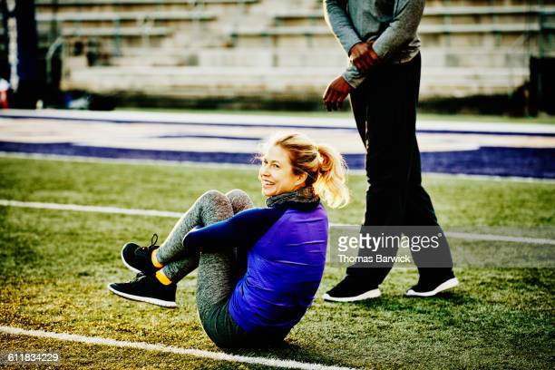 Smiling female athlete resting during workout