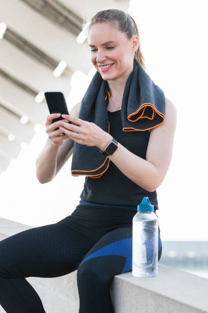 Smiling female athlete with water bottle using smart phone while sitting on retaining wall