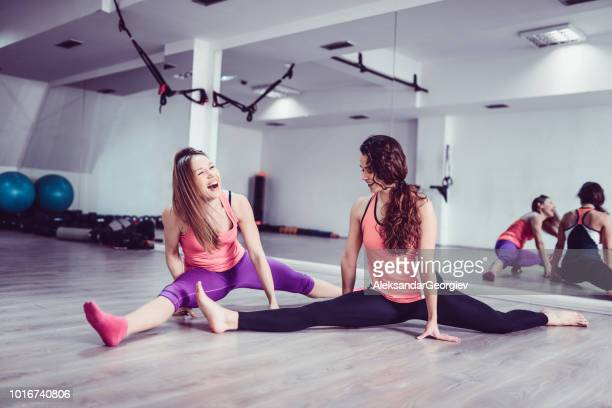 Smiling Female Athletes Doing A Difficult Full Split Exercise
