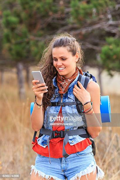 Smiling female backpacker using smart phone in mountain