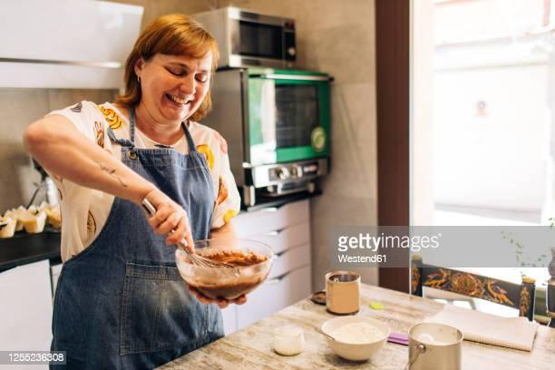 smiling female baker mixing cake batter in bowl on table at workshop - female whipping stock-fotos und bilder