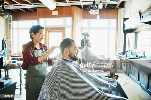 Smiling female barber combing clients hair during hair cut in barber shop