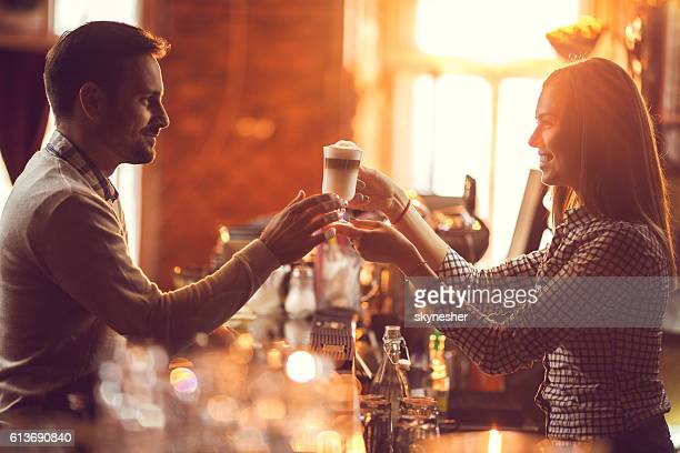 Smiling female bartender giving coffee to male customer.