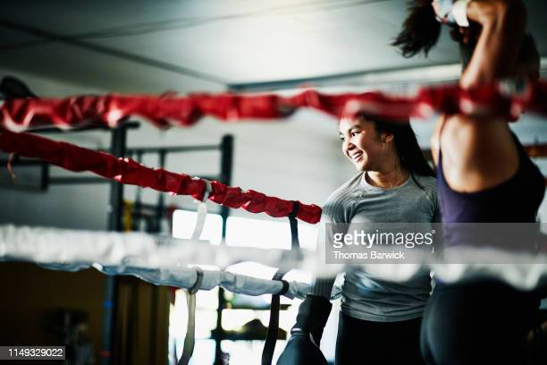 smiling female boxer working out in boxing ring in gym - boxeo deporte fotografías e imágenes de stock