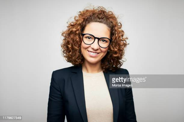 smiling female brunette ceo wearing eyeglasses - waist up stock pictures, royalty-free photos & images