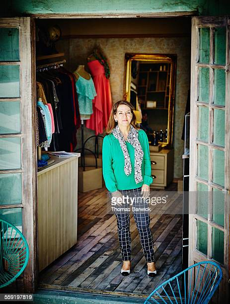 Smiling female business owner standing in boutique