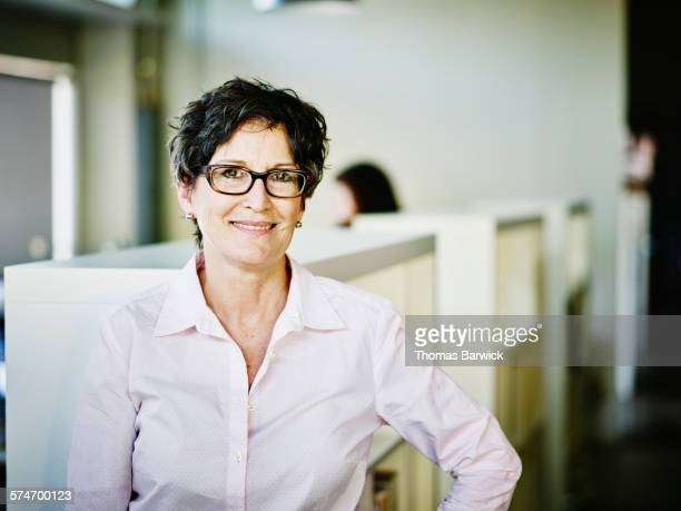 Smiling female business owner standing in office