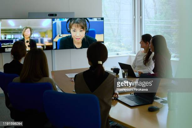 smiling female business owner talking during presentation during meeting in office conference room - テレビ会議 ストックフォトと画像