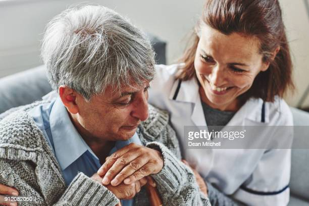 smiling female carer with senior man at care home - janitor stock photos and pictures