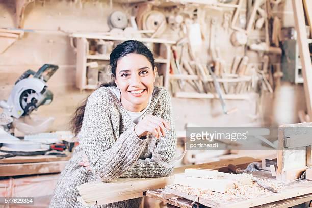 Smiling female carpenter at workshop