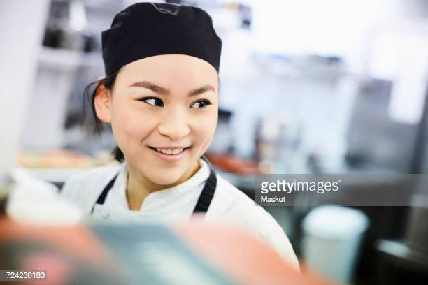 Smiling female chef looking away in commercial kitchen