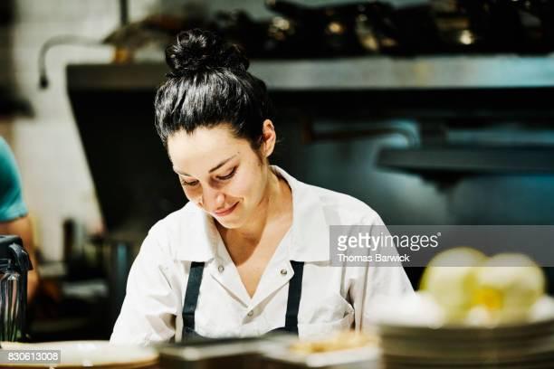 Smiling female chef working in restaurant kitchen
