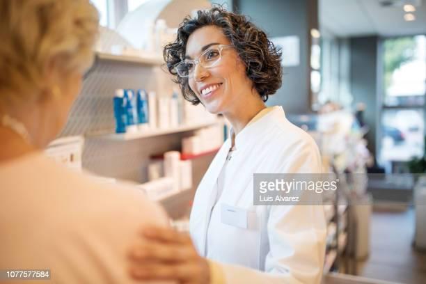 smiling female chemist consoling costumer at pharmacy - hand auf der schulter stock-fotos und bilder