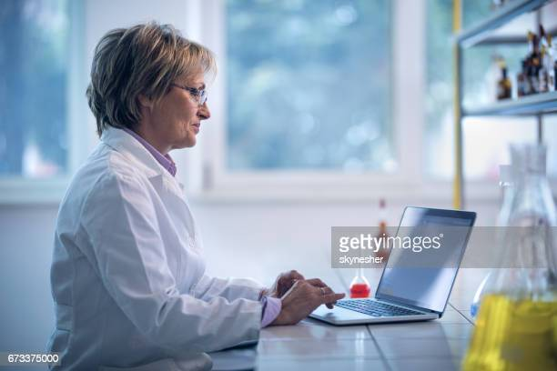 Smiling female chemist using laptop for medical research in a laboratory.