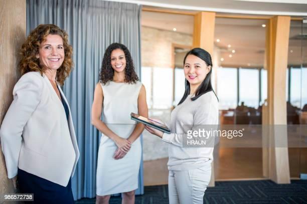 Sourire des collègues féminines debout dans la salle du Conseil