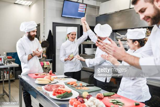 smiling female cook getting praised by colleagues after winning vegetable cutting competition - contest stock pictures, royalty-free photos & images