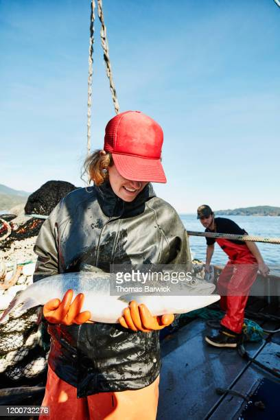 smiling female crew member of fishing boat holding chum salmon on deck of boat - catch of fish stock pictures, royalty-free photos & images
