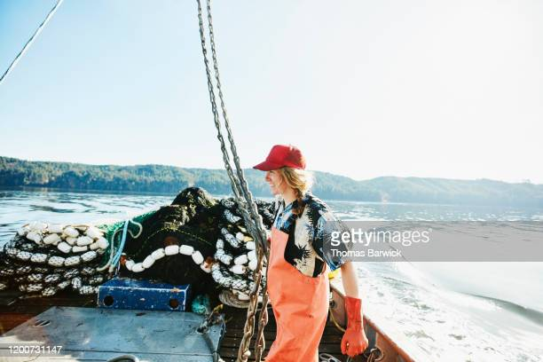 smiling female crew member organizing gear on deck of fishing boat - leanincollection stock pictures, royalty-free photos & images