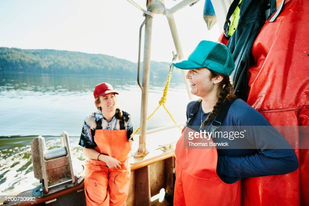 smiling female crew of fishing boat in discussion on deck of boat - fishing industry stock pictures, royalty-free photos & images