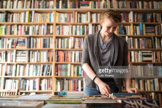Smiling female customer choosing book against bookshelf