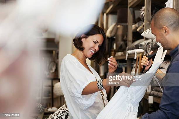 Smiling female customer looking at white dress held by owner in store