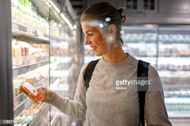 smiling female customer reading ingredient while shopping in supermarket - strap stock pictures, royalty-free photos & images