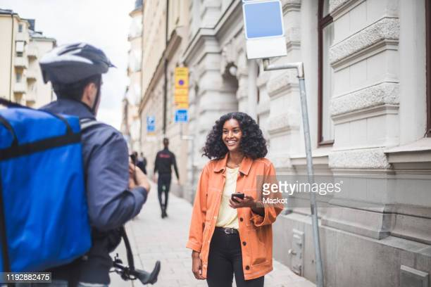 smiling female customer talking with food delivery man while standing on sidewalk - bicycle messenger stock pictures, royalty-free photos & images