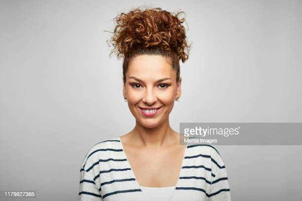 smiling female design professional with hair bun - gelockt stock-fotos und bilder