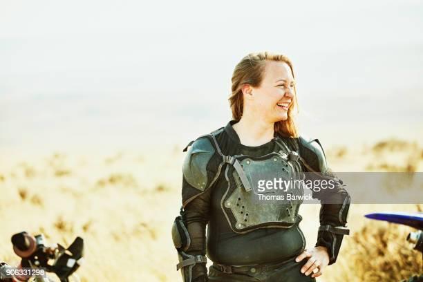 Smiling female dirt bike rider resting during desert ride