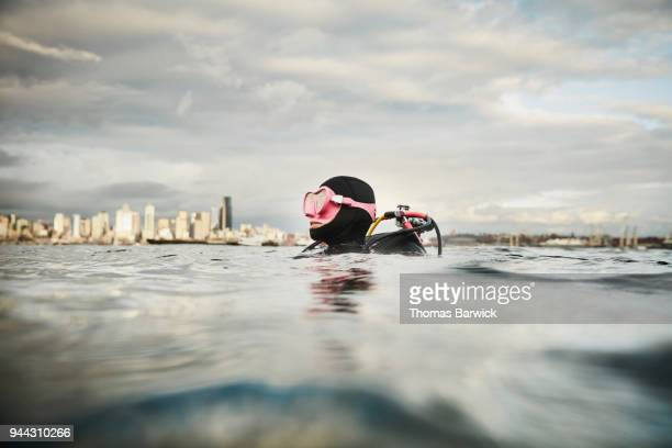 Smiling female diver at surface of water before open water dive with cityscape in background
