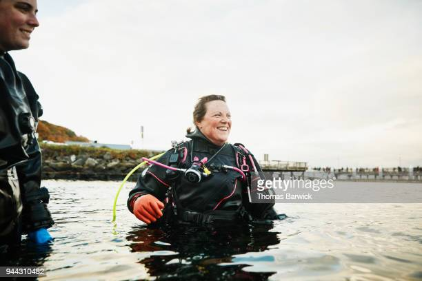 Smiling female diver in discussion with friends while standing in water after open water dive