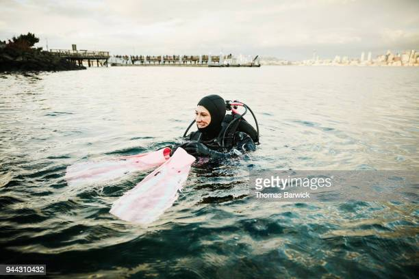 Smiling female diver putting on fins before open water dive