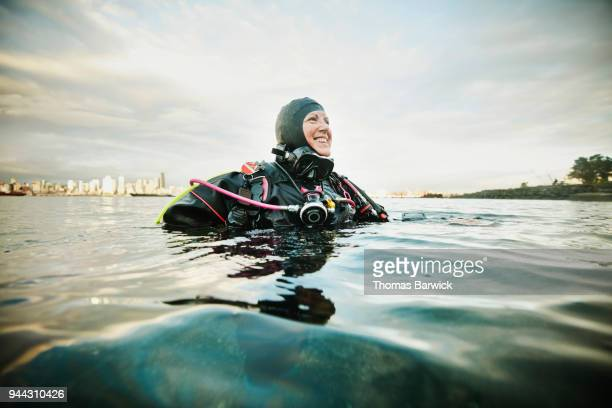 Smiling female diver standing in water near shoreline after open water dive