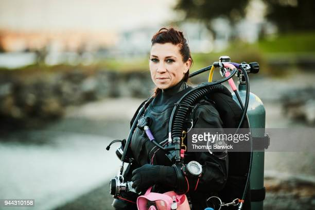 Smiling female diver standing on beach after open water dive
