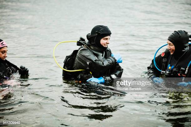 Smiling female divers entering the water for open water dive