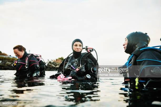 Smiling female divers in discussion at shoreline after open water dive
