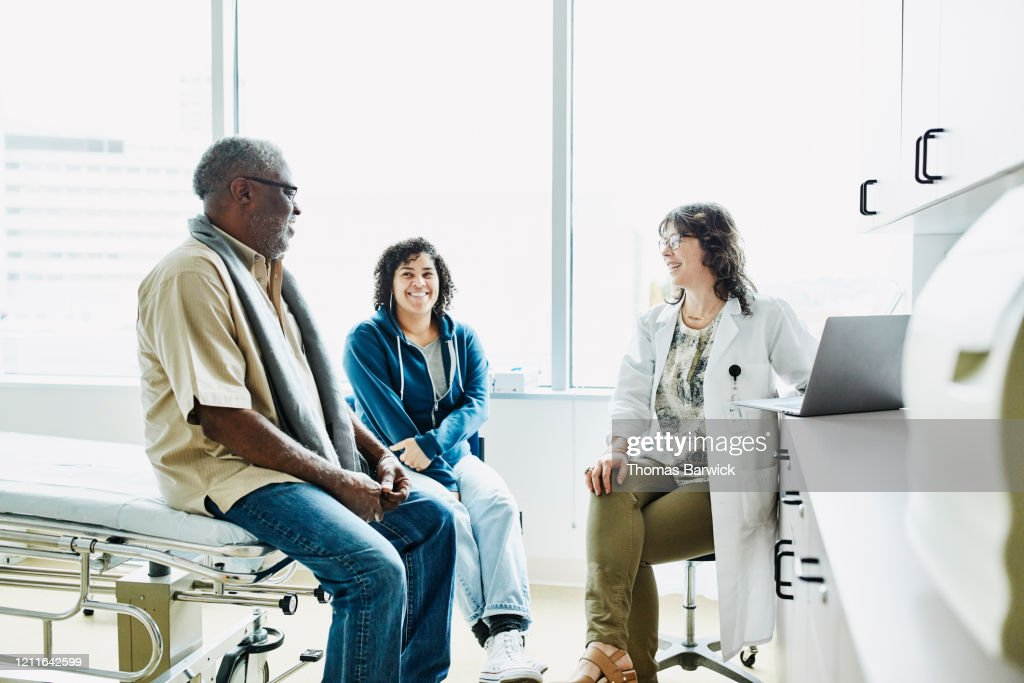 Smiling female doctor consulting with senior male patient and adult daughter in exam room : Stockfoto