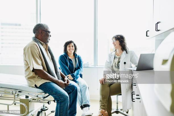 smiling female doctor consulting with senior male patient and adult daughter in exam room - patient photos et images de collection