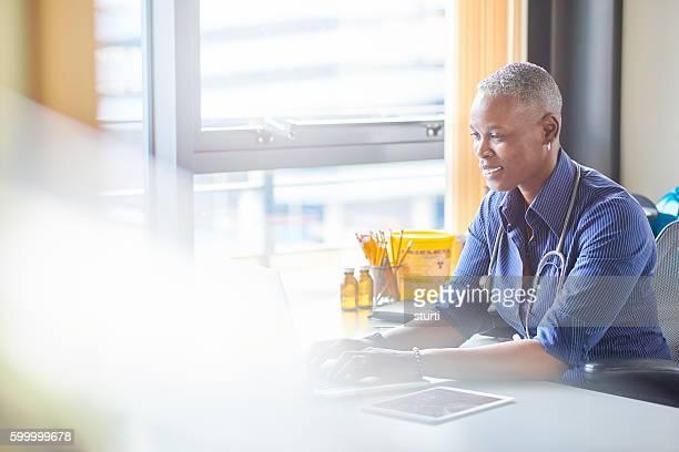 smiling female doctor sitting at her desk