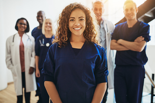 Smiling female doctor standing with medical colleagues in a hospital 1058457940