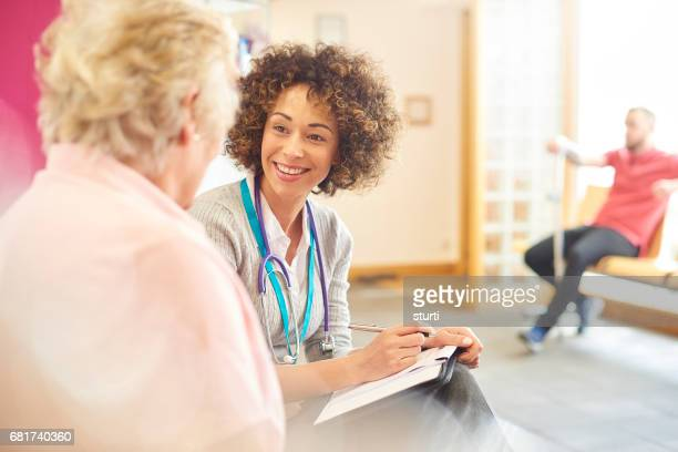 Smiling female doctor with senior patient