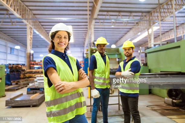 smiling female engineer against male colleagues - engineer stock pictures, royalty-free photos & images