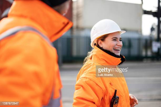 smiling female engineer at the shipyard - schutzhelm stock-fotos und bilder