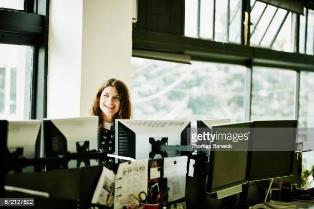Smiling female engineer coding in high tech start up office