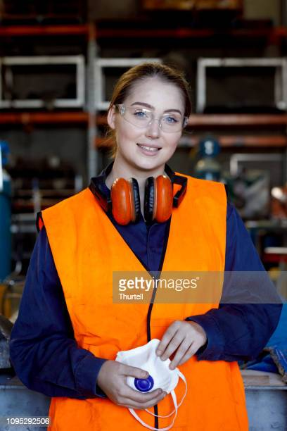 smiling female engineer wearing protective clothing in workshop - ear protection stock pictures, royalty-free photos & images