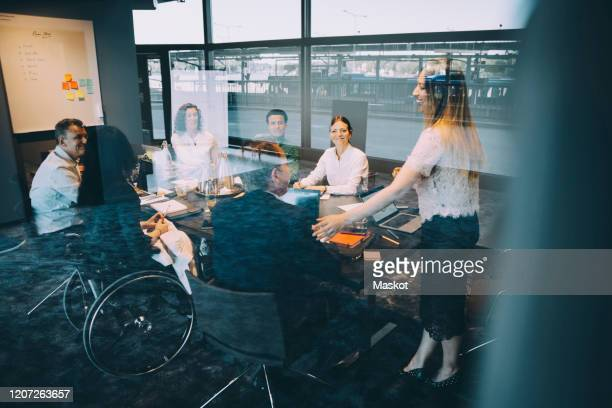 smiling female entrepreneur discussing strategy with coworkers in board room at office - differing abilities female business fotografías e imágenes de stock