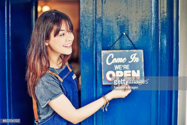 Smiling female entrepreneur hanging open sign on deli door